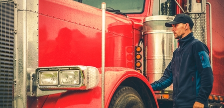 Photo pour Automotive industry. Modern Truck Transportation. Caucasian Trucker in Front of His Red Shiny Truck. - image libre de droit