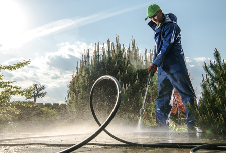 Photo pour Garden Washing Maintenance. Caucasian Worker in His 30s with Pressure Washer Cleaning Brick Paths. - image libre de droit