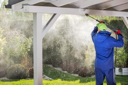 Photo pour Porch Roof Power Cleaning. Caucasian Men with Pressure Washer. - image libre de droit
