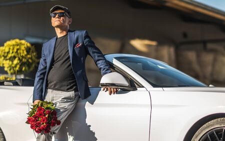 Foto de Dating Caucasian Senior in His 60s with Roses in Front of His Convertible Car. - Imagen libre de derechos