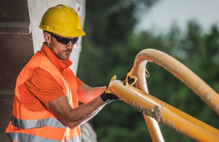 Photo for Caucasian Worker with High Voltage Plastic Pipe. Underground Electric Line Installation. Construction Industry. - Royalty Free Image