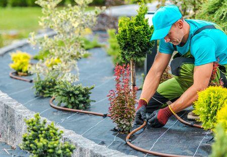 Photo pour Professional Caucasian Gardener Building Plants Irrigation System in Developed Garden. Industrial Theme. - image libre de droit