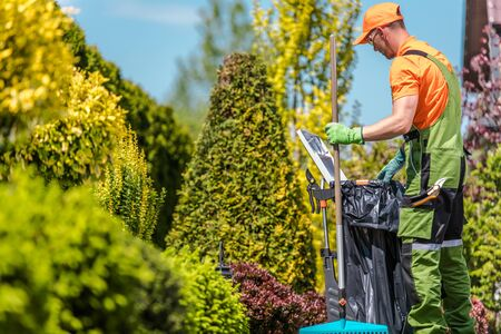 Photo pour Gardener with His Garden Tools and the Seasonal Maintenance. Caucasian Men in His 30s. - image libre de droit