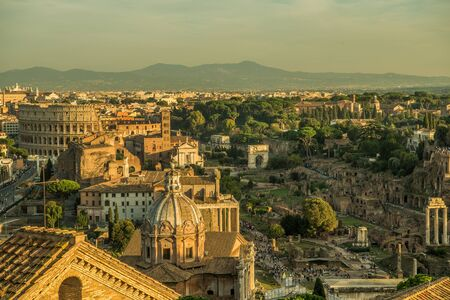 Foto per Roman Forum Ruins and Colosseum. Ancient Government Buildings in the Center of Rome, Italy. Famous Travel Destination.   - Immagine Royalty Free