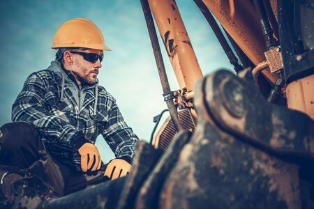 Photo pour Close Up Of Male Construction Worker Checking Excavator Before Staring Job.  - image libre de droit