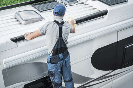 Photo for Recreational Vehicles Industry Theme. Caucasian RV Service Worker Washing Camper Van Roof Using Large Soft Sponge and Cleaning Detergent. - Royalty Free Image