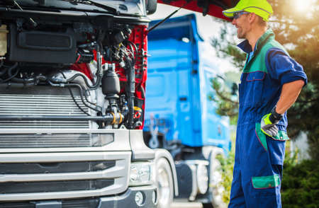 Foto für Happy Smiling Caucasian Professional Truck Mechanic in His 30s Staying Next to Semi Truck Tractor with Open Hood. Vehicle Maintenance Theme. Heavy Duty Transportation Servicing. - Lizenzfreies Bild