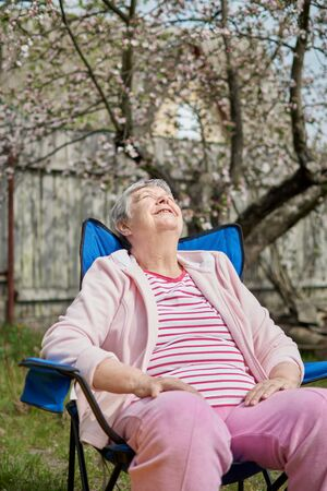 Side head shot view tranquil calm middle aged hoary woman sitting on camping chair alone. Peaceful mindful mature senior grandmother daydreaming relaxing meditating outdors. Enjoy retire.