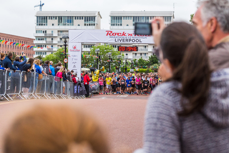 A group of runners wait at the start line of the 2017 Liverpool Rock n Roll marathon seen on 28 May 2017 by the Albert Dock through a gap in the spectators.