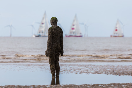 An Iron Man watches the start of the 2017/18 round the world Clipper race on a beach near Liverpool.The Clipper Race (now in its eleventh year) sees twelve global teams compete in a 40000 nautical mile around the world race on a 70 foot ocean racing yacht
