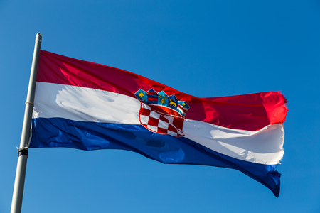 A large Croatian flag flies patriotically above the old fortress in Hvar Town, the highest peak in the area.