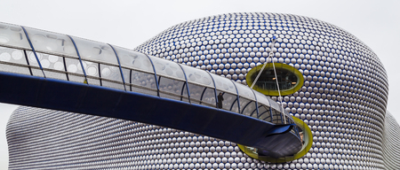 A man walks along the curved footbridge towards the iconic Selfridges Building in the heart of Birmingham city centre.  The building, which is part of the Bullring shopping centre was completed in 2003.  The facade comprises 15000 anodised aluminium discs