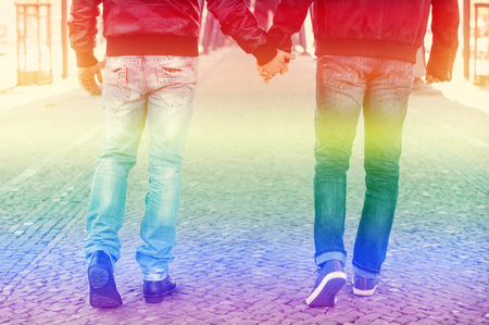 two men walking and holding hands with the rainbow colors for gay pride