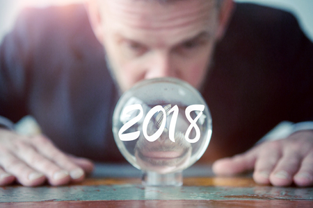 closeup of businessman looking at glass ball with the number 2018