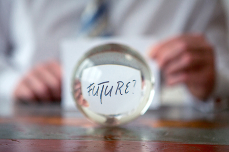 closeup of man holding paper with the word Future in front of glass ball