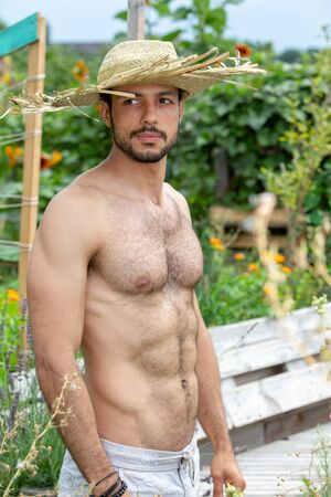 Foto de handsome hairy shirtless man with straw hat standing in garden - Imagen libre de derechos