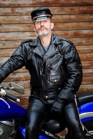 Photo pour portrait of sexy biker dressed in black leather sitting on his bike - image libre de droit