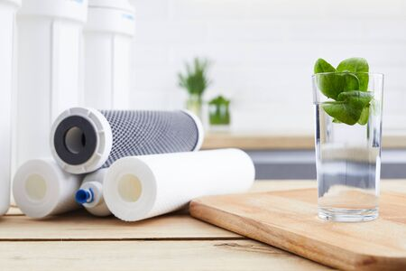 Photo pour A glass of clean water with osmosis filter and cartridges on wooden table in kitchen interior. Concept Household filtration system. - image libre de droit