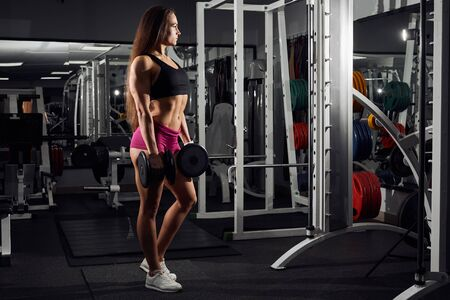 Photo for Brutal athletic girl pumping up muscules with dumbbells and showing her trained body . - Royalty Free Image
