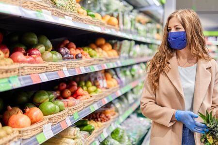 Photo pour Shopping during the coronavirus Covid-19 pandemic. Woman in facial mask and gloves buys citrus fruit at market. - image libre de droit