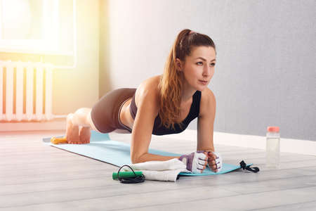 Photo pour Woman In Fitness Wear Doing Exercise At Home. Time for yoga. healthy girl doing exercises while resting at home. Fitness, relaxation, stay home concept - image libre de droit