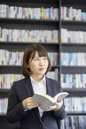 Photo pour Woman reading a book in front of a bookshelf - image libre de droit