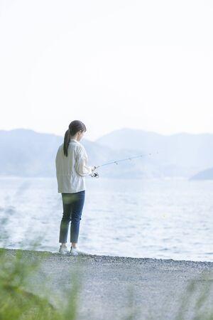Photo pour Young woman enjoying fishing at the seaside - image libre de droit
