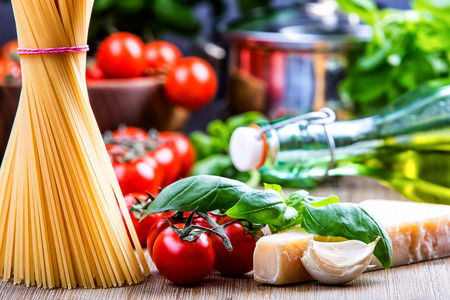Italian and Mediterranean food ingredients on old wooden background.spaghetti olives basil cherry tomato pesto pasta garlic pepper olive oil and mortar.