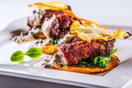 Culinary kitchen. French cuisine. Recipe: Confit pork cheeks with green spinach leaves celery pancakes fried mushroom sauce and fried celery decoration.