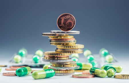 Euro money and medicaments. Euro coins and pills. Coins stacked on each other in different positions and freely pills scattered around. Reimbursement of medicinal products in health care.
