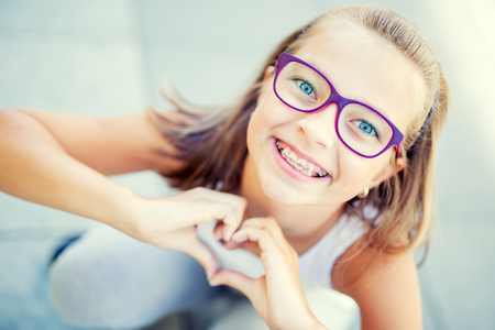 Photo pour Smiling little girl in with braces and glasses showing heart with hands. - image libre de droit