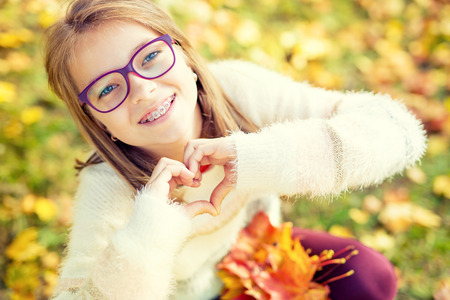 Foto de Smiling little girl with braces and glasses showing heart with hands.Autum time. - Imagen libre de derechos