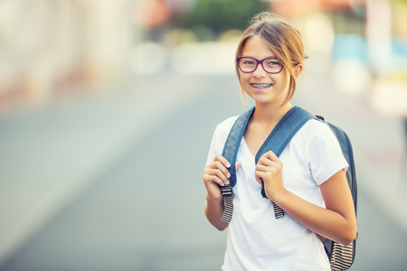 Foto de Schoolgirl with bag, backpack. Portrait of modern happy teen school girl with bag backpack. Girl with dental braces and glasses. - Imagen libre de derechos