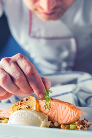 Photo for Chef in hotel or restaurant kitchen cooking, only hands. Prepared salmon steak with dill decoration. - Royalty Free Image