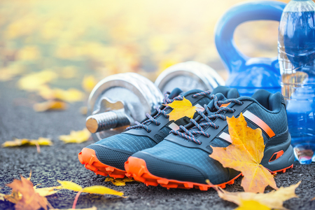 Foto de Pair of blue sport shoes water and  dumbbells laid on a path in a tree autumn alley with maple leaves -  accessories for run exercise or workout activity. - Imagen libre de derechos