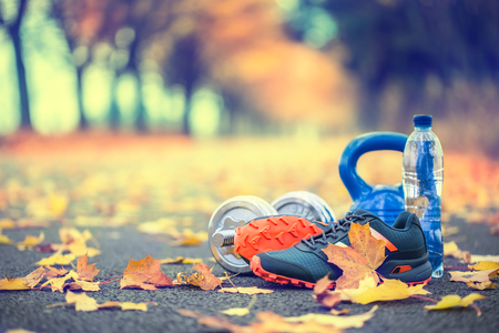 Photo for Pair of blue sport shoes water and  dumbbells laid on a path in a tree autumn alley with maple leaves -  accessories for run exercise or workout activity. - Royalty Free Image