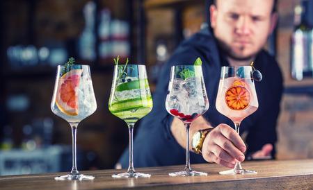 Photo pour Barman in pub or restaurant  preparing a gin tonic cocktail drinks in wine glasses. - image libre de droit