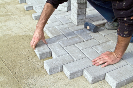 Foto de Bricklayer prfessional at work on the sidewalk saves tiles. - Imagen libre de derechos