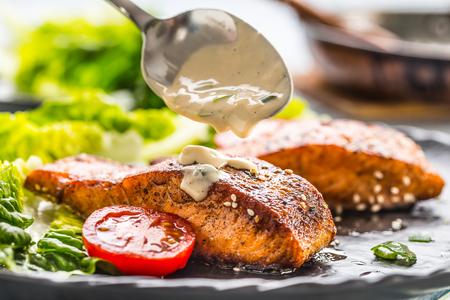 Foto de Delicious grilled roasted salmon fillets or steaks with mushroom sauce sesame tomatoes and lettuce salad. - Imagen libre de derechos