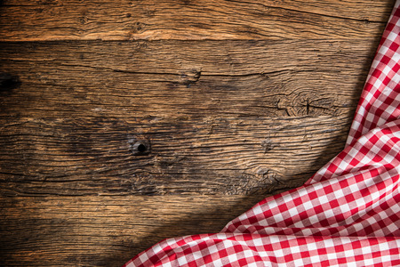 Photo pour Red checkered kitchen tablecloth on rustic wooden table. - image libre de droit