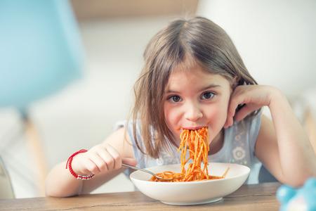 Foto de Cute little kid girl eating spaghetti bolognese at home. - Imagen libre de derechos