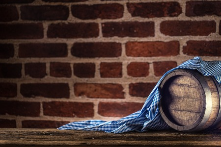 Photo for Oktoberfest wooden barrel and blue tablecloth on rustic oak table. - Royalty Free Image