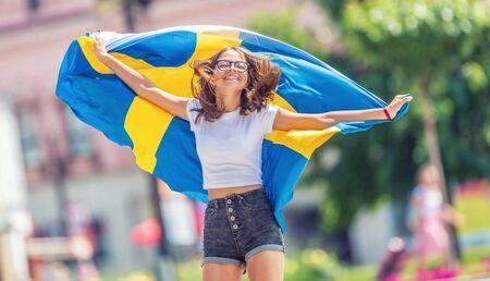 Photo pour Happy girl tourist walking in the street with sweden flag. - image libre de droit