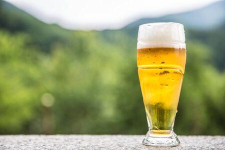Foto de Draft light beer on stone table somwhere in nature. - Imagen libre de derechos