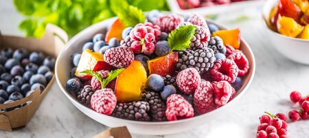 Foto per Frozen fruits blueberries blackberry raspberry red currant peach and herbs melissa. - Immagine Royalty Free