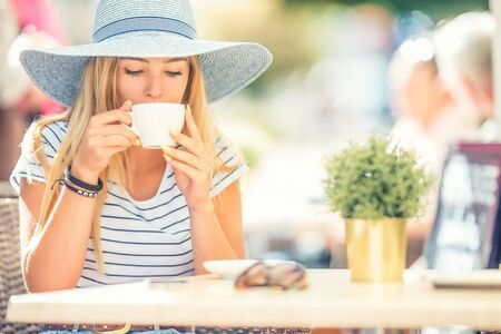 Photo pour Beautiful girl drinking coffee in a cafe terrace. Summer portrait young woman. - image libre de droit