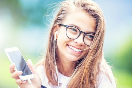 Photo for Young teenage girl with headphones enjoying with good music. Modern young woman with cellphone. - Royalty Free Image