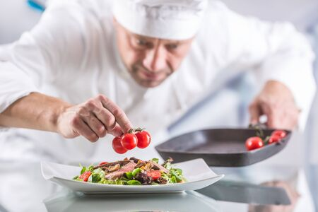 Photo for Chef in the kitchen of the hotel or restaurant decorates the food just before serving. - Royalty Free Image