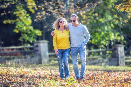 Foto für Happy mature couple in autumn park in the embrace walk on the fallen maple leaves. - Lizenzfreies Bild