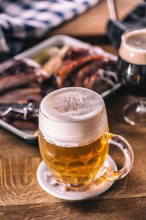 Photo pour Glass of light beer in pub or restavurant on table with delicoius food. - image libre de droit